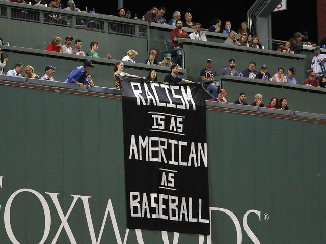 Green Monster draped with 'Racism is as American as baseball' sign