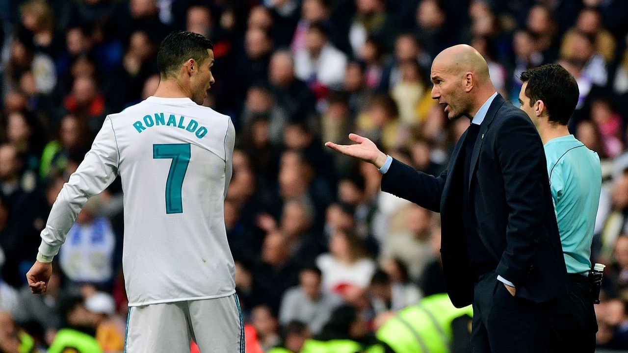 Real Madrid's French coach Zinedine Zidane (R) speaks to Real Madrid's Portuguese forward Cristiano Ronaldo during the Spanish league football match between Real Madrid and Sevilla at the Santiago Bernabeu Stadium in Madrid on December 9, 2017. / AFP PHOTO / PIERRE-PHILIPPE MARCOU
