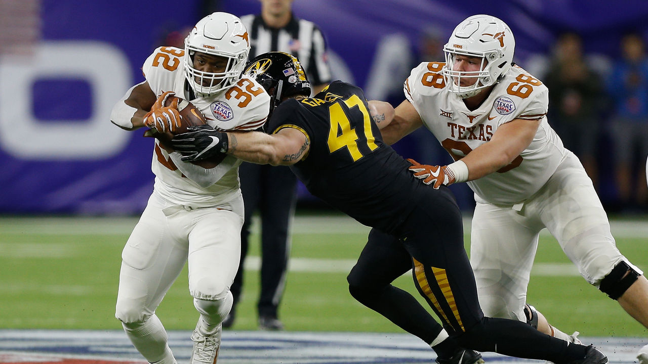 HOUSTON, TX - DECEMBER 27: Daniel Young #32 of the Texas Longhorns attempts to break the tackle of Cale Garrett #47 of the Missouri Tigers as Derek Kerstetter #68 blocks during the Academy Sports & Outdoors Bowl at NRG Stadium on December 27, 2017 in Houston, Texas.