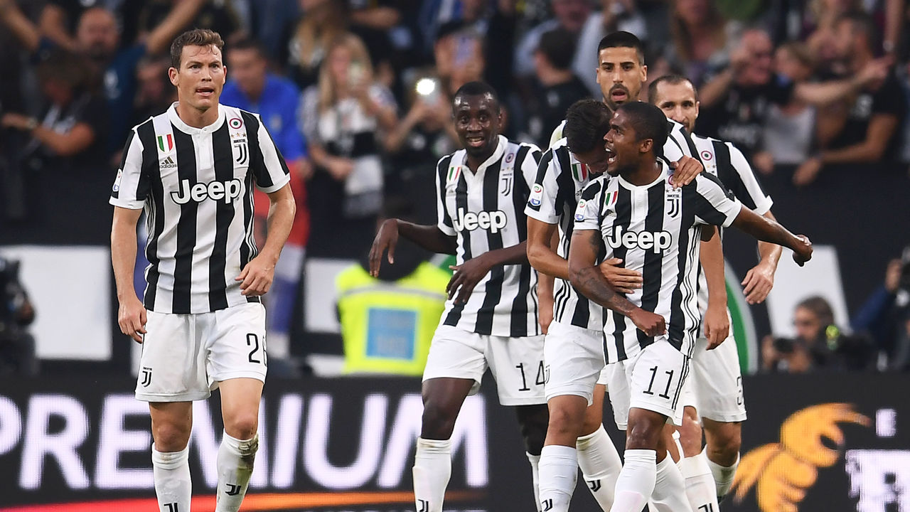 Juventus' midfielder Douglas Costa from Brazil (R) celebrates with teammates after scoring during the Italian Serie A football match Juventus Vs Lazio on October 14, 2017 at the 'Allianz Stadium' in Turin. / AFP PHOTO / MARCO BERTORELLO