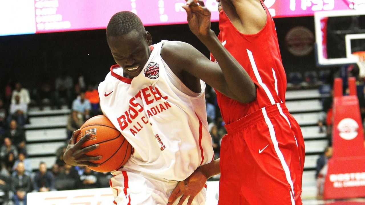 TORONTO, ON - APRIL 11 - Matur Maker of team white drives past O'Shae Brissett of team red during the second half of basketball action during the Biosteel All Canadian game. (Carlos Osorio/Toronto Star via Getty Images)