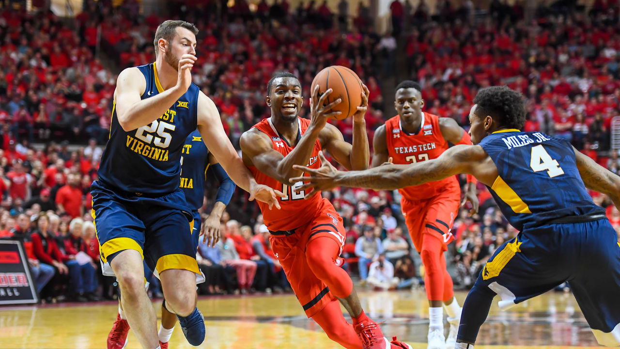 LUBBOCK, TX - JANUARY 13: Keenan Evans #12 of the Texas Tech Red Raiders goes to the basket against Maciej Bender #25 of the West Virginia Mountaineers and Daxter Miles Jr. #4 of the West Virginia Mountaineers during the first half of the game on January 13, 2018 at United Supermarket Arena in Lubbock, Texas.