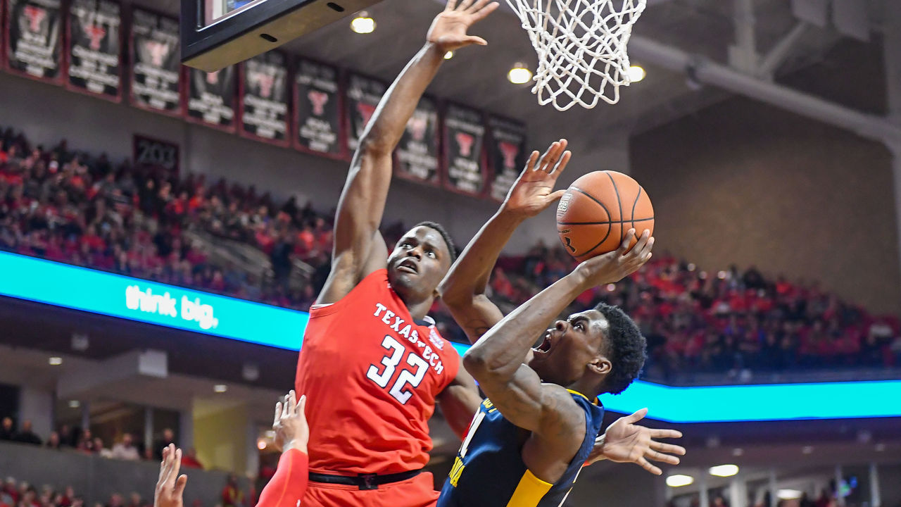 LUBBOCK, TX - JANUARY 13: Wesley Harris #21 of the West Virginia Mountaineers shoots the ball over Norense Odiase #32 of the Texas Tech Red Raiders during the game on January 13, 2018 at United Supermarket Arena in Lubbock, Texas.