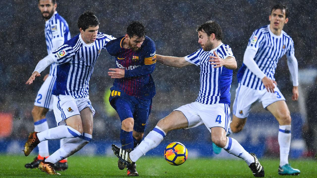 SAN SEBASTIAN, SPAIN - JANUARY 14: Lionel Messi of FC Barcelona competes for the ball withIgor Zubeldia (L) and Asier Illarramendi of Real Sociedad de Futbol during the La Liga match between Real Sociedad and FC Barcelona at Anoeta stadium on January 14, 2018 in San Sebastian, Spain.
