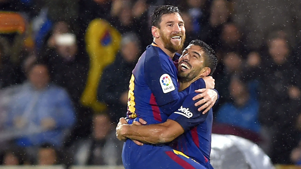 Barcelona's Argentinian forward Lionel Messi (L) is congratulated by teammate Uruguayan forward Luis Suarez after scoring their team's fourth goal during the Spanish league football match between Real Sociedad and FC Barcelona at the Anoeta stadium in San Sebastian on January 14, 2018. / AFP PHOTO / ANDER GILLENEA