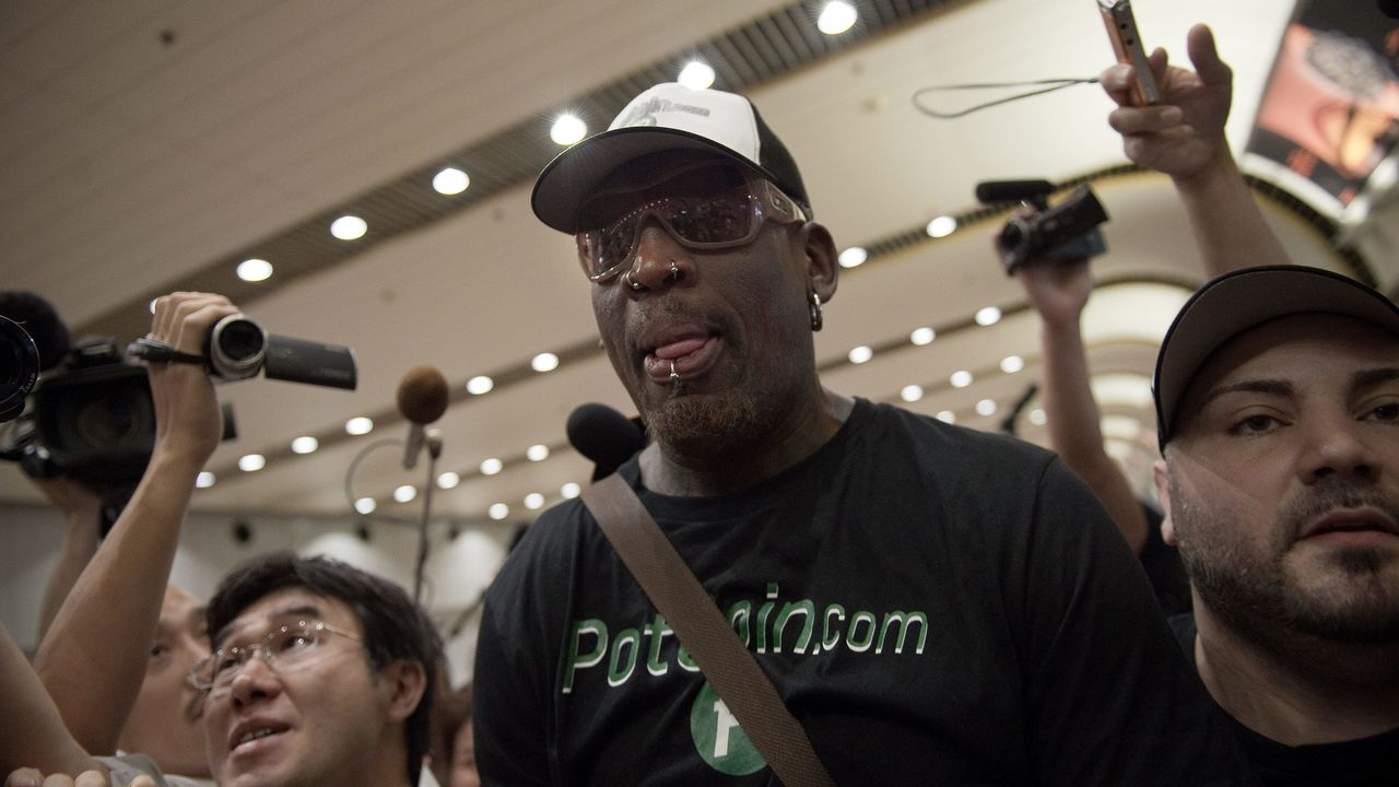 Former NBA basketball player Dennis Rodman (C) of the US is mobbed by the media as he walks out from the arrival gate returning from his trip to North Korea at Beijing's international airport on June 17, 2017. Rodman passed through Beijing after his latest jaunt to North Korea. / AFP PHOTO / NICOLAS ASFOURI