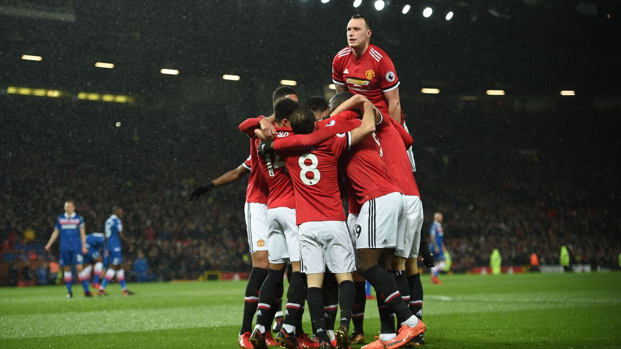 Manchester United's English defender Phil Jones (R) jumps onto the celebration after Manchester United's Ecuadorian midfielder Antonio Valencia scored the opening goal during the English Premier League football match between Manchester United and Stoke City at Old Trafford in Manchester, north west England, on January 15, 2018. / AFP PHOTO / Oli SCARFF /