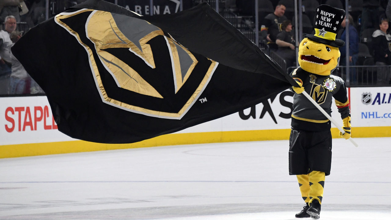LAS VEGAS, NV - DECEMBER 31: The Vegas Golden Knights mascot Chance the Golden Gila Monster waves a Knights flag at center ice after the team defeated the Toronto Maple Leafs 6-3 at T-Mobile Arena on December 31, 2017 in Las Vegas, Nevada.