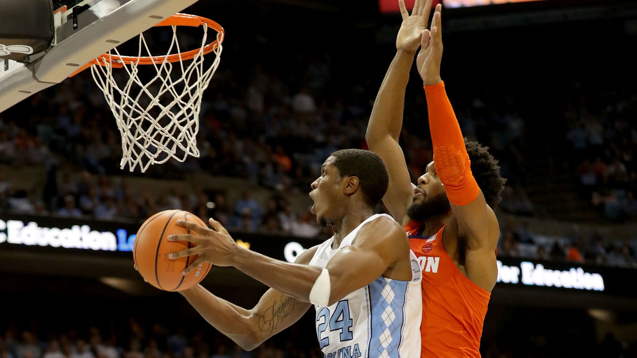 CHAPEL HILL, NC - JANUARY 16: Kenny Williams #24 of the North Carolina Tar Heels drives to the basket against Gabe DeVoe #10 of the Clemson Tigers during their game at Dean Smith Center on January 16, 2018 in Chapel Hill, North Carolina.