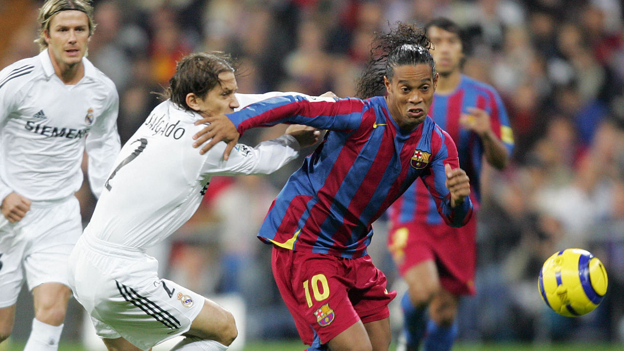 Madrid, SPAIN: Real Madrid's Michel Salgado (L) vies with Barcelona's Ronaldinho (R) during their Spanish League football match at Santiago Bernabeu stadium in Madrid, 19 November, 2005. AFP PHOTO JAVIER SORIANO