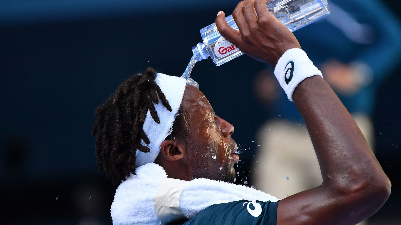 France's Gael Monfils cools off with a bottle of water during his men's singles second round match against Serbia's Novak Djokovic on day four of the Australian Open tennis tournament in Melbourne on January 18, 2018. / AFP PHOTO / Greg Wood / -- IMAGE RESTRICTED TO EDITORIAL USE - STRICTLY NO COMMERCIAL USE --