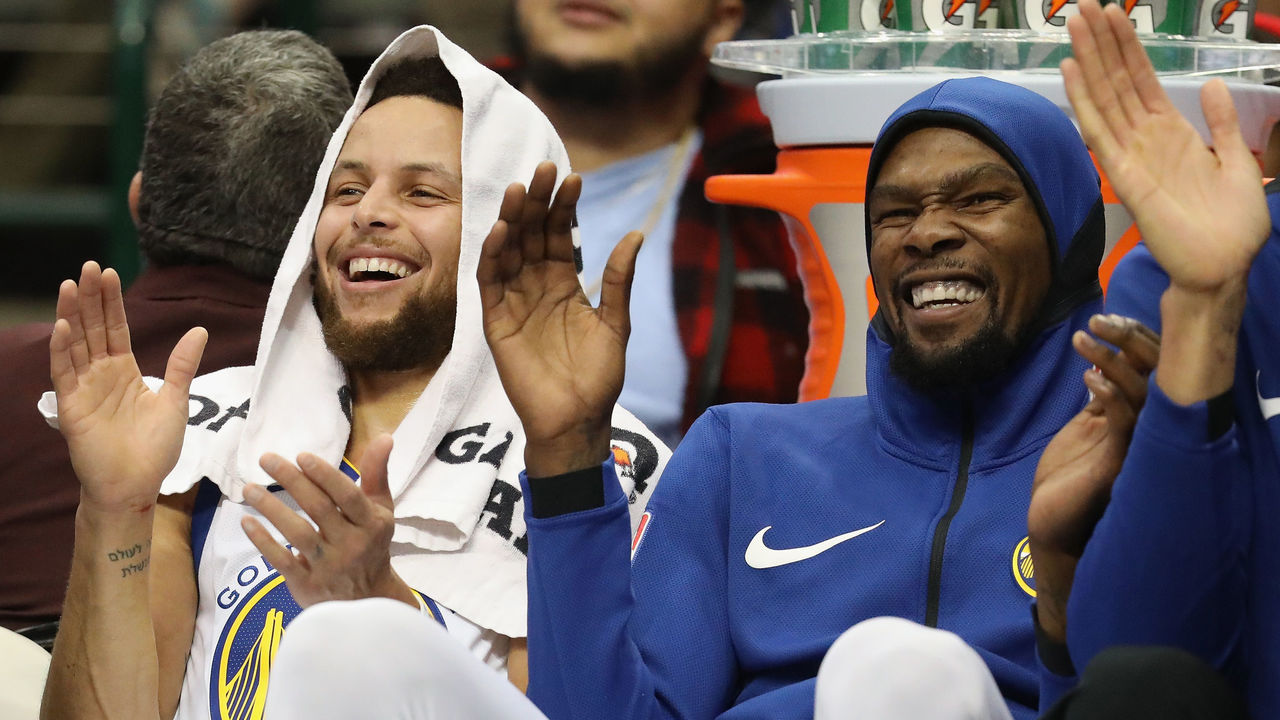 DALLAS, TX - JANUARY 03: (L-R) Stephen Curry #30 and Kevin Durant #35 of the Golden State Warriors share a laugh during play against the Dallas Mavericks at American Airlines Center on January 3, 2018 in Dallas, Texas.