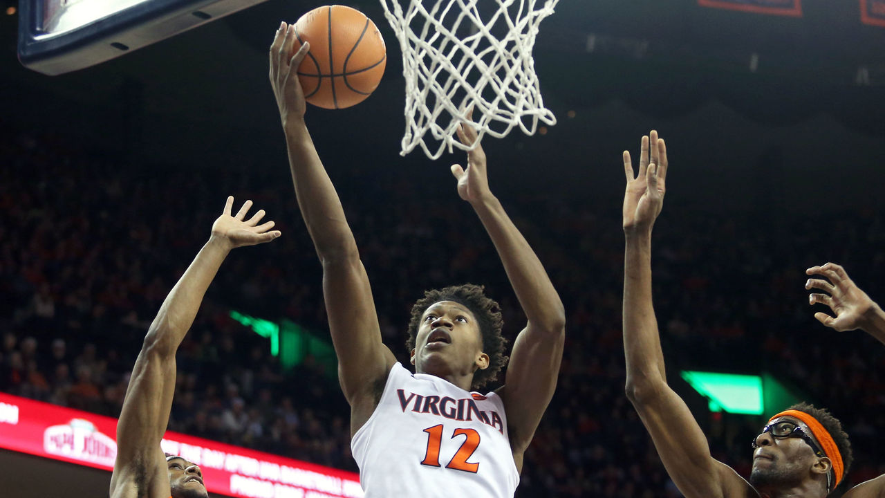 CHARLOTTESVILLE, VA - JANUARY 9: De'Andre Hunter #12 of the Virginia Cavaliers shoots between Oshae Brissett #11 and Paschal Chukwu #13 of the Syracuse Orange in the first half during a game at John Paul Jones Arena on January 9, 2018 in Charlottesville, Virginia.