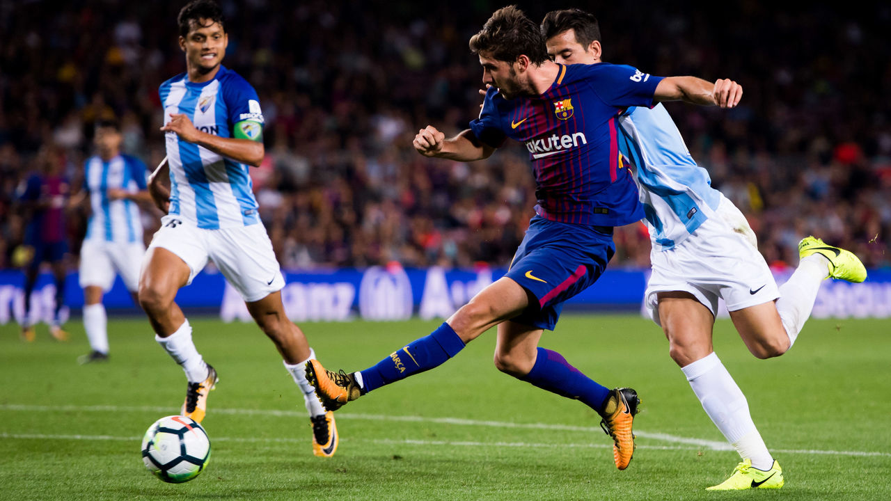 BARCELONA, SPAIN - OCTOBER 21: Sergi Roberto of FC Barcelona shoots the ball under pressure from Luis Hernandez of Malaga CF during the La Liga match between Barcelona and Malaga at Camp Nou on October 21, 2017 in Barcelona, Spain.