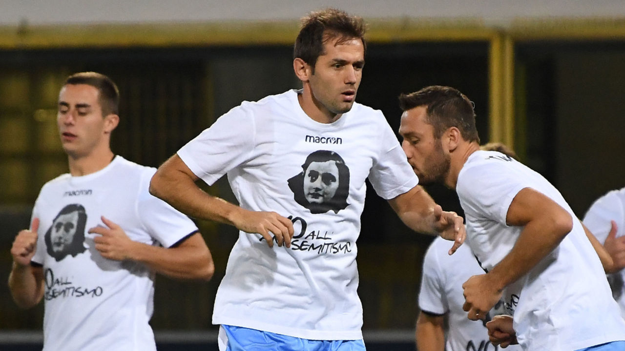 Lazio's midfielder from Bosnia-Herzegovina Senad Lulic (C) and teammates wear t-shirts against antisemitism showing an image of holocaust victim Anne Frank, during the warm up prior the Italian Serie A football match Bologna vs Lazio on October 25, 2017 at the Renato-Dall'Ara stadium in Bologna. Emotions were still running high in Italy, days after Lazio fans posted anti-semitic photos of Anne Frank in a Roma jersey in the stands of the Stadio Olimpico. The Italian football federation announced that there will be a minute's reflection on the Holocaust before every match and a passage read from 'The Diary of Anne Frank'. At the same time referees and captains will hand out copies of the diary and Italian Jewish writer Primo Levi's memoir 'If This Is A Man'. / AFP PHOTO / Gianni SCHICCHI