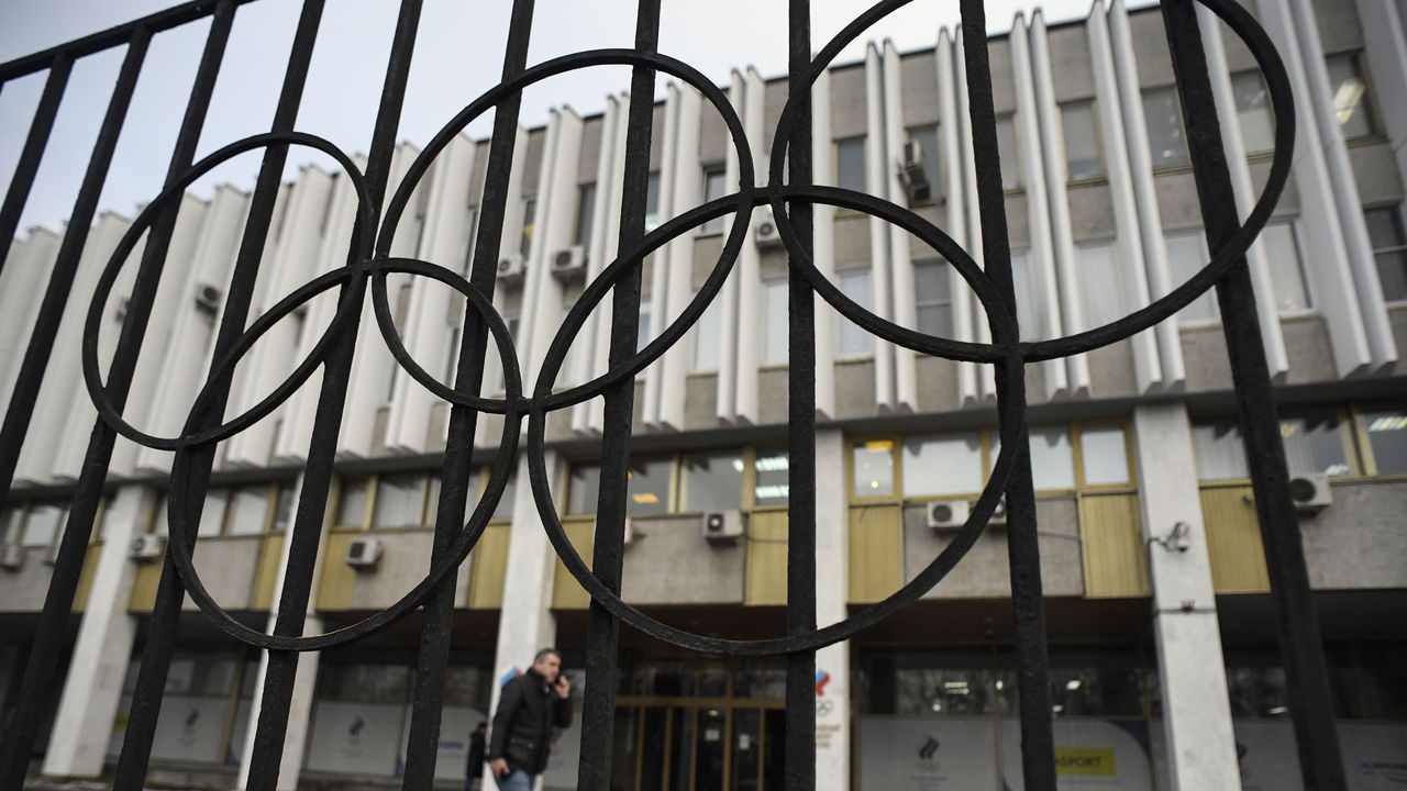A man talks on the phone in front of the headquarters of the Russian Olympic Committee in Moscow on December 12, 2017. Most Russian athletes want to compete in the 2018 Winter Olympic Games in Pyeongchang despite a ban on the country's team, the head of the athletes' commission at the Russian Olympic Committee (ROC) said on December 11. / AFP PHOTO / Alexander NEMENOV