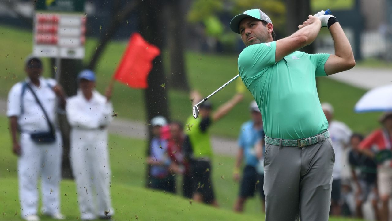 Sergio Garcia of Spain plays a shot along the fairway during round three of the Singapore Open golf tournament at the Serapong golf course in Singapore on January 20, 2018. / AFP PHOTO / ROSLAN RAHMAN