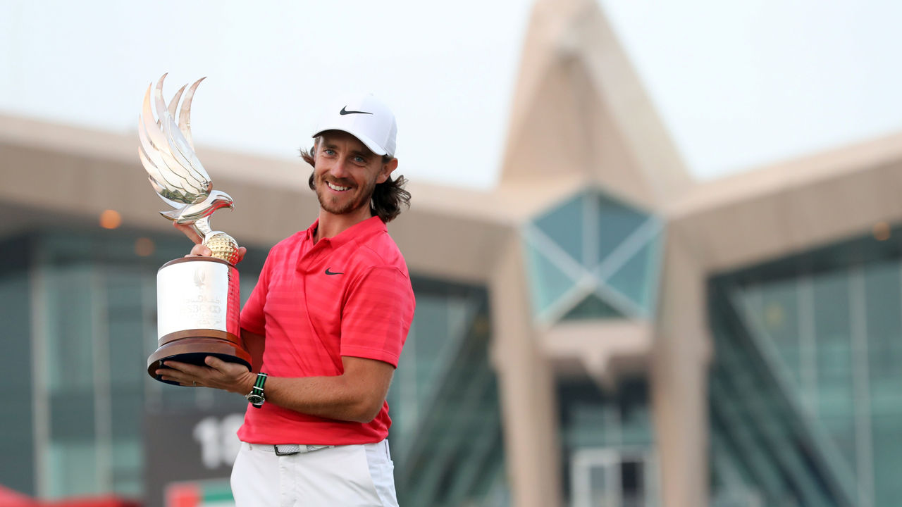 Tommy Fleetwood of England poses with the winner's trophy while celebrating his victory at the Abu Dhabi HSBC Golf Championship, at the Abu Dhabi Golf Club on January 21, 2018. Fleetwood successfully defended his title at the $3 million Abu Dhabi Championship, shooting a seven-under par 65 round to beat compatriot Ross Fisher by two shots. / AFP PHOTO / KARIM SAHIB
