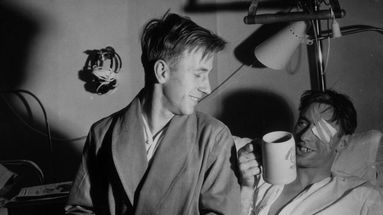 11th February 1958: Drinking out of a Bavarian beer tankard Raymond Wood shares a laugh with Bobby Charlton (left) in a Munich hospital. They are two of the survivors of the Munich Air disaster which killed several footballers and journalists.