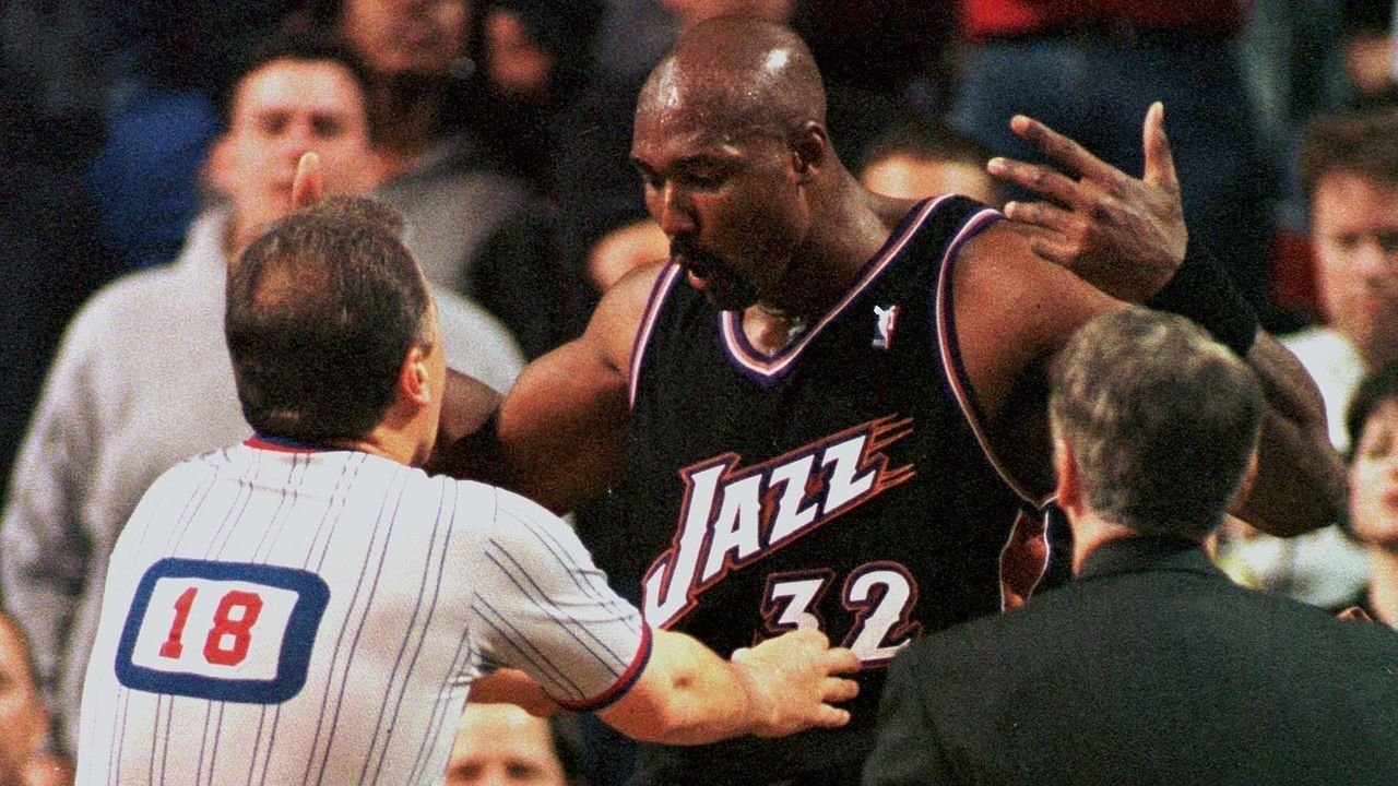 SEATTLE, UNITED STATES: Karl Malone (C) of the Utah Jazz argues with referee Mark Wunderlich (L) as Utah assistant coach Phil Johnson(R) approaches during game 4 of the first round of the Western Conference Playoffs, against the Seattle SuperSonics 03 May 2000 in Seattle. Seattle won the game 104-93, to even the series 2-2. AFP PHOTO DAN LEVINE