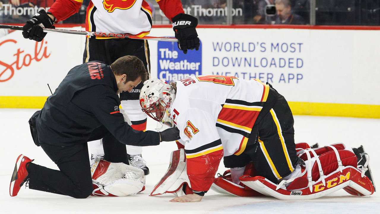 NEW YORK, NY - FEBRUARY 11: A trainer tends to Mike Smith #41 of the Calgary Flames during the final moments of a 3-2 win against the New York Islanders at Barclays Center on February 11, 2018 in the Brooklyn borough of New York City.
