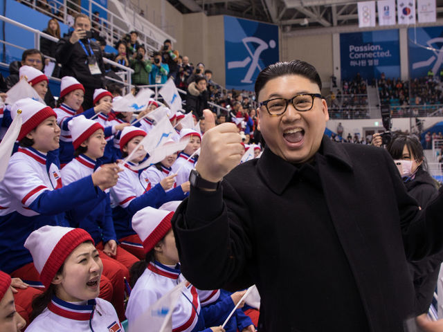 A man impersonating North Korean leader Kim Jong Un gestures as he stands before North Korean cheerleaders attending the Unified Korean ice hockey game against Japan during the Pyeongchang 2018 Winter Olympic Games at the Kwandong Hockey Centre in Gangneung on February 14, 2018. / AFP PHOTO / YELIM LEE