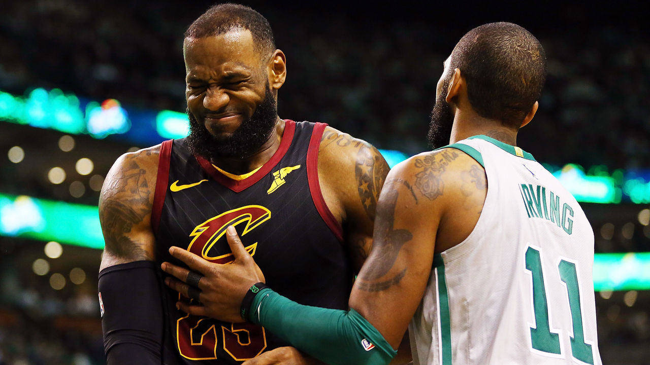 BOSTON, MA - FEBRUARY 11: Lebron James #23 of the Cleveland Cavaliers reacts with Kyrie Irving #11 of the Boston Celtics during the first quarter of a game at TD Garden on February 11, 2018 in Boston, Massachusetts.