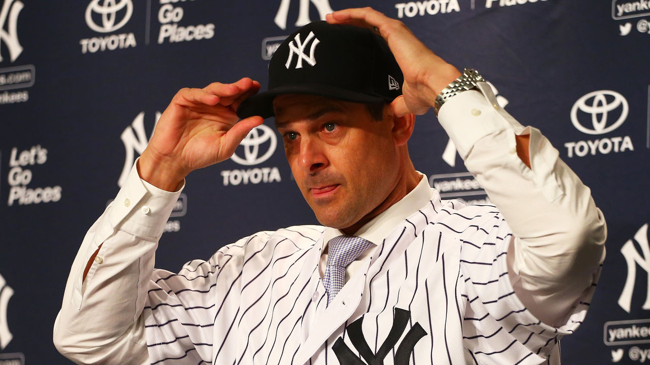 NEW YORK, NY - DECEMBER 06: Aaron Boone puts on a Yankee cap after being introduced as manager of the New York Yankees at Yankee Stadium on December 6, 2017 in the Bronx borough of New York City.