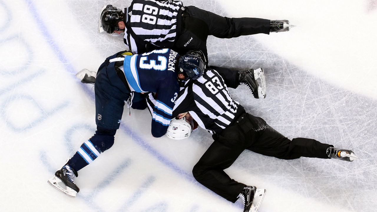 WINNIPEG, MB - FEBRUARY 16: Linesman Steve Miller #89 and Matt MacPherson #83 work to separate Dustin Byfuglien #33 of the Winnipeg Jets and A.J. Greer #24 of the Colorado Avalanche after a second period tilt at the Bell MTS Place on February 16, 2018 in Winnipeg, Manitoba, Canada.
