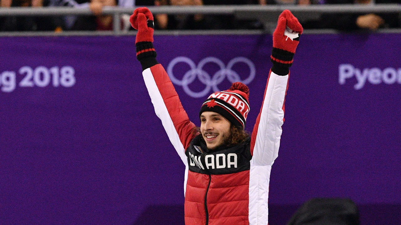 Canada's Samuel Girard celebrates on the podium for winning gold in the men's 1,000m short track speed skating venue ceremony during the Pyeongchang 2018 Winter Olympic Games, at the Gangneung Ice Arena in Gangneung on February 17, 2018. / AFP PHOTO / Mladen ANTONOV