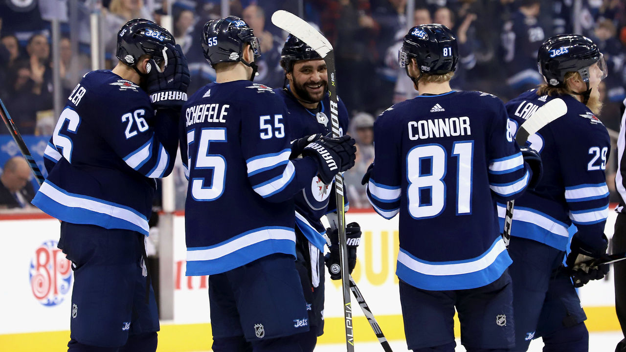 WINNIPEG, MB - FEBRUARY 16: Blake Wheeler #26, Mark Scheifele #55, Dustin Byfuglien #33, Kyle Connor #81 and Patrik Laine #29 of the Winnipeg Jets head to the bench after celebrating a second period goal against the Colorado Avalanche at the Bell MTS Place on February 16, 2018 in Winnipeg, Manitoba, Canada.