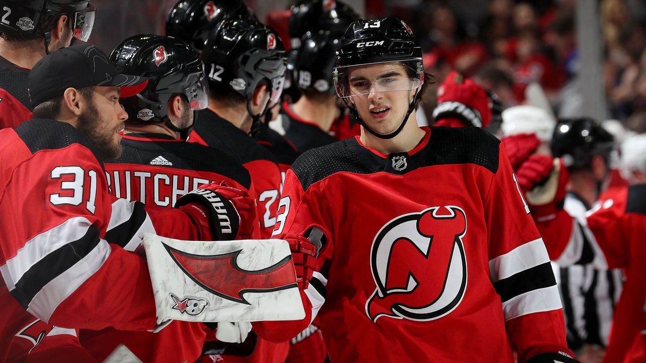 NEWARK, NJ - FEBRUARY 15: Nico Hischier #13 of the New Jersey Devils celebrates his goal with teammate Eddie Lack #31 as he skates by the bench in the third period against the Carolina Hurricanes on February 15, 2018 at Prudential Center in Newark, New Jersey.The New Jersey Devils defeated the Carolina Hurricanes 5-2.