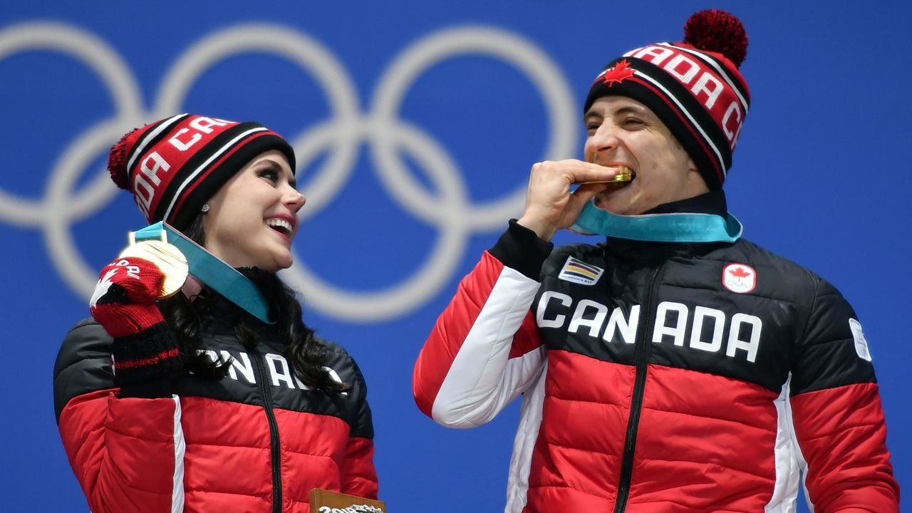 Canada's gold medallists Tessa Virtue (L) and Scott Moir pose on the podium during the medal ceremony for the figure skating ice dance at the Pyeongchang Medals Plaza during the Pyeongchang 2018 Winter Olympic Games in Pyeongchang on February 20, 2018. / AFP PHOTO / Fabrice COFFRINI