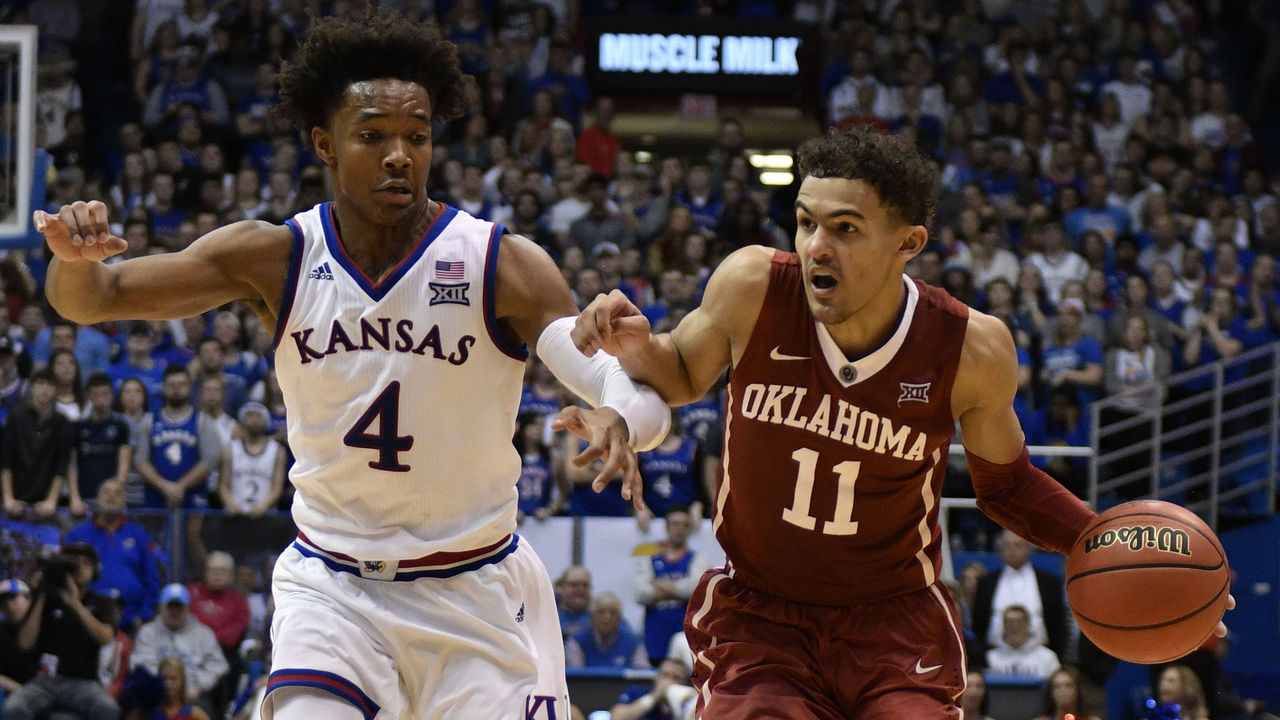 LAWRENCE, KS - FEBRUARY 19: Trae Young #11 of the Oklahoma Sooners drives to the basket as he is defended by Devonte' Graham #4 of the Kansas Jayhawks in the second half at Allen Fieldhouse on February 19, 2018 in Lawrence, Kansas.