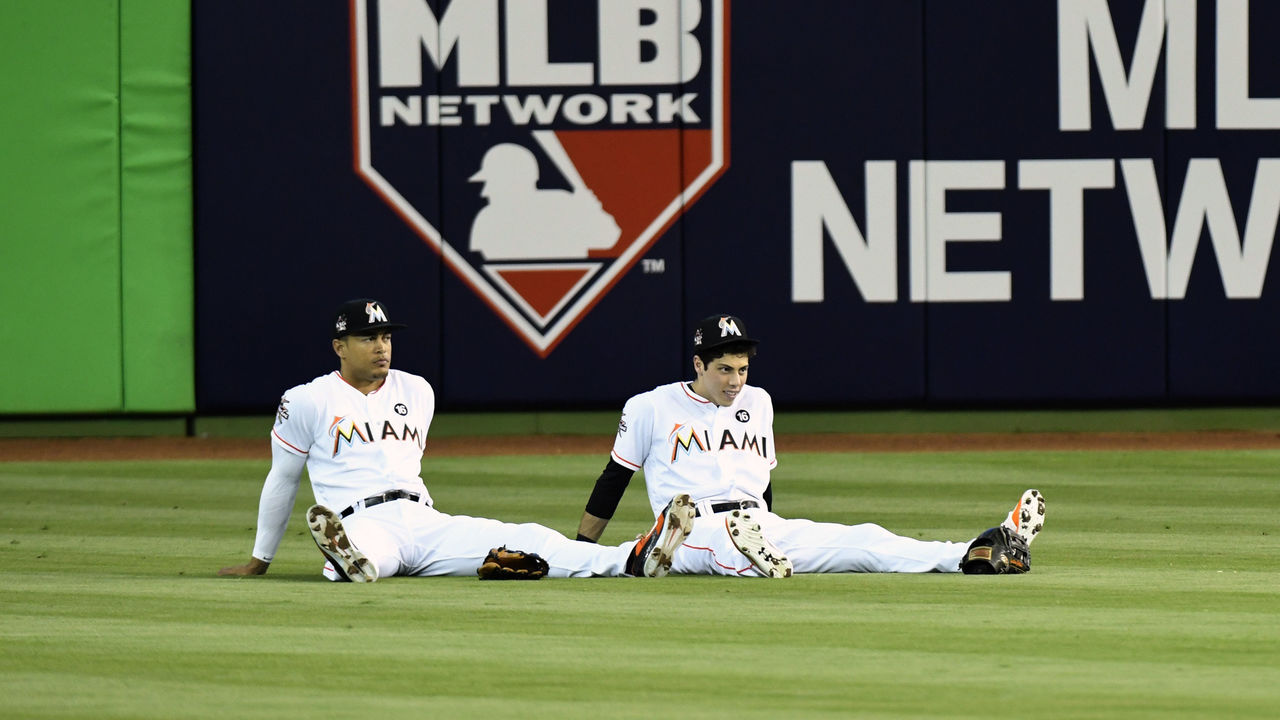 MIAMI, FL - APRIL 12: Giancarlo Stanton #27 and Christian Yelich #21 of the Miami Marlins sit in the outfield during a power outage in the 4th inning of the game against the Atlanta Braves at Marlins Park on April 12, 2017 in Miami, Florida.