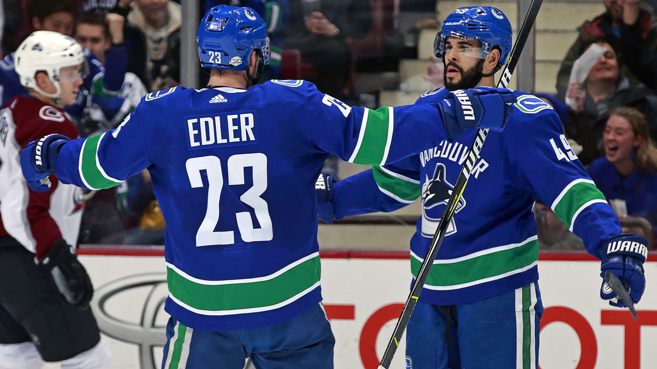 VANCOUVER, BC - FEBRUARY 20: Darren Archibald #49 of the Vancouver Canucks is congratulated by Alexander Edler #23 after scoring during their NHL game at Rogers Arena February 20, 2018 in Vancouver, British Columbia, Canada.