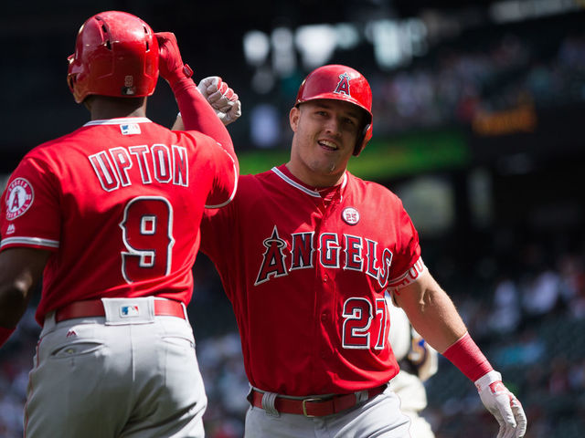 SEATTLE, WA - SEPTEMBER 10: Mike Trout #27 of the Los Angeles Angels of Anaheim celebrates his solo home run in the first inning with Justin Upton #9 against the Seattle Mariners at Safeco Field on September 10, 2017 in Seattle, Washington.