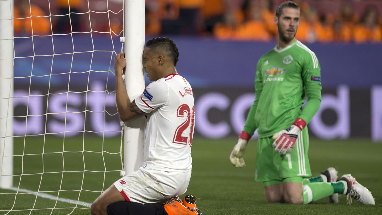 Sevilla's Colombian forward Luis Muriel (L) reacts next to Manchester United's Spanish goalkeeper David de Gea during the UEFA Champions League round of 16 first leg football match Sevilla FC against Manchester United at the Ramon Sanchez Pizjuan stadium in Sevilla on February 21, 2018. / AFP PHOTO / JORGE GUERRERO