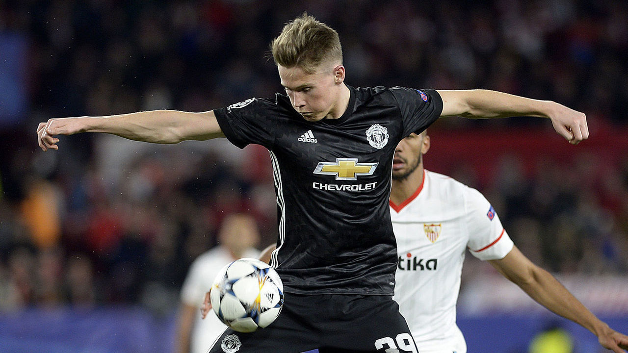 Manchester United's English midfielder Scott McTominay (L) jumps for the ball with Sevilla's French midfielder Steven N'Zonzi (R) during the UEFA Champions League round of 16 first leg football match Sevilla FC against Manchester United at the Ramon Sanchez Pizjuan stadium in Sevilla on February 21, 2018. / AFP PHOTO / Cristina Quicler