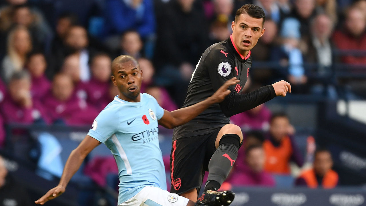 MANCHESTER, ENGLAND - NOVEMBER 05: Granit Xhaka of Arsenal takes on Fernandinho of Man City during the Premier League match between Manchester City and Arsenal at Etihad Stadium on November 5, 2017 in Manchester, England.