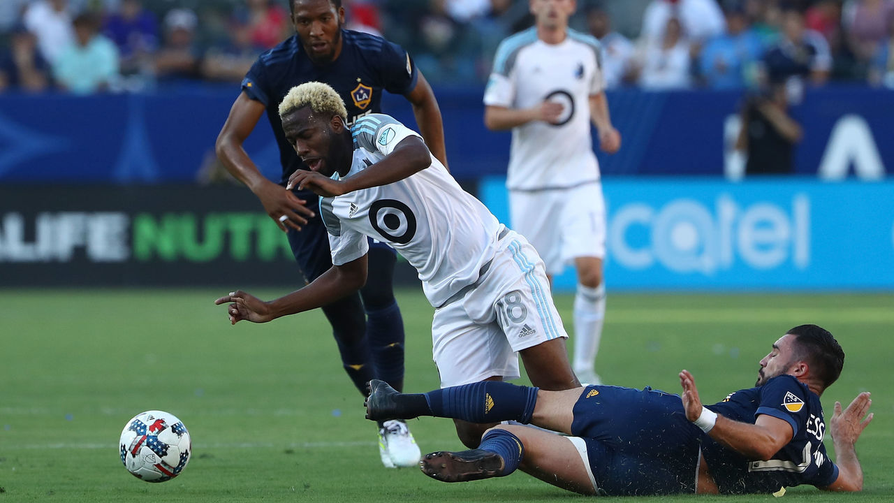CARSON, CA - OCTOBER 15: Romain Alessandrini #7 of the Los Angele Galaxy tackles Kevin Molino #18 of Minnesota United FC in the first half during the MLS game at StubHub Center on October 15, 2017 in Carson, California.