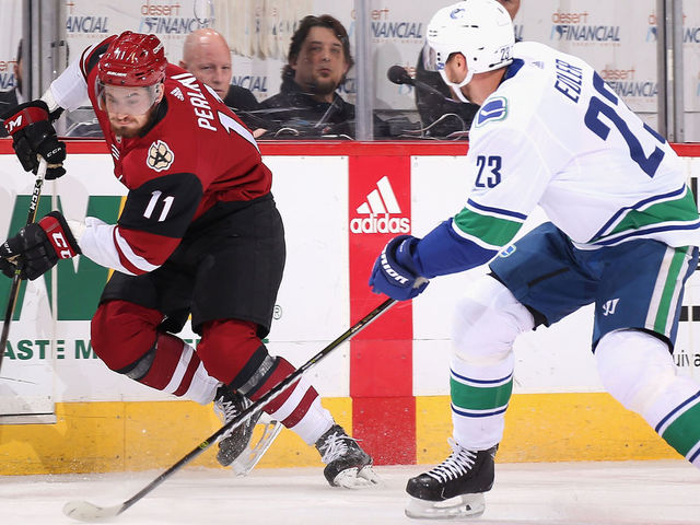 GLENDALE, AZ - FEBRUARY 25: Brendan Perlini #11 of the Arizona Coyotes skates the puck past Alexander Edler #23 of the Vancouver Canucks during the first period of the NHL game at Gila River Arena on February 25, 2018 in Glendale, Arizona. The Canucks defeated the Coyotes 3-1