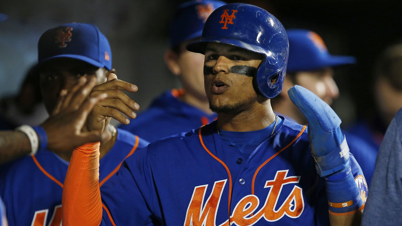 NEW YORK, NY - SEPTEMBER 25: Juan Lagares #12 of the New York Mets is congratulated after scoring on a double by Travis d'Arnaud #18 in the third inning against the Atlanta Braves during the second game of a doubleheader at Citi Field on September 25, 2017 in the Flushing neighborhood of the Queens borough of New York City.