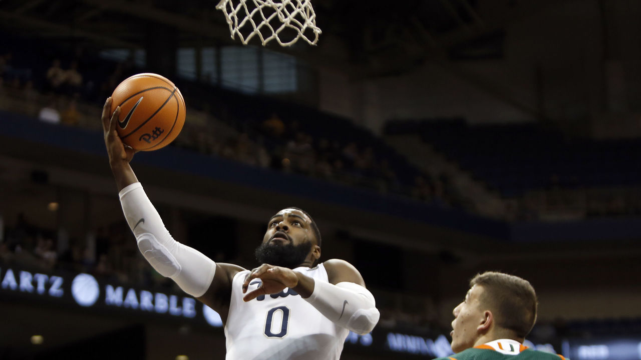 PITTSBURGH, PA - DECEMBER 30: Jared Wilson-Frame #0 of the Pittsburgh Panthers lays one in against Dejan Vasiljevic #1 of the Miami Hurricanes during the game at Petersen Events Center on December 30, 2017 in Pittsburgh, Pennsylvania.