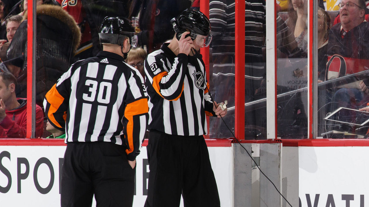 OTTAWA, ON - MARCH 9: Referees Kendrick Nicholson #30 and Mike Hasenfratz #27 get ready to review a goal from a coach's challenge during a game between the Ottawa Senators and the Calgary Flames at Canadian Tire Centre on March 9, 2018 in Ottawa, Ontario, Canada. *** Local Caption ***