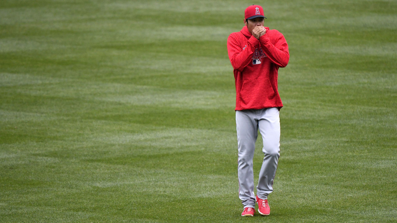 KANSAS CITY, MO - APRIL 14: Shohei Ohtani #17 of the Los Angeles Angels of Anaheim blows in his hands to keep them warm as he stretches out prior to a game against the Kansas City Royals at Kauffman Stadium on April 14, 2018 in Kansas City, Missouri.