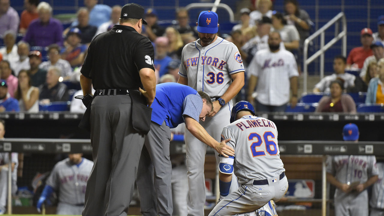 MIAMI, FL - APRIL 11: Manager Mickey Callaway #36 of the New York Mets and Head Athletic Trainer Brian Chicklo talk with Kevin Plawecki #26 after he was hit by a pitch in the eighth inning against the Miami Marlins at Marlins Park on April 11, 2018 in Miami, Florida.